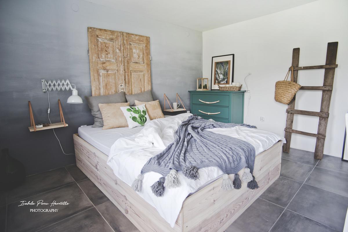 drewniane łóżko, zagłówek ze starych drewnianych drzwi, lampa nożycowa, zielona komoda, skandynawskie wnętrze