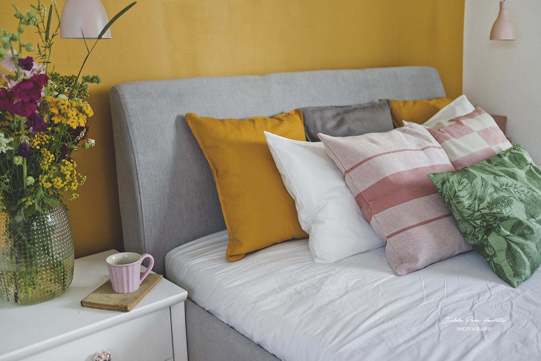 sypialnia, miodowa ściana, tapicerowane łóżko, bukiet polnych kwiatów, lampki nocne, kapelusze na ścianie,kolorowe wnętrze