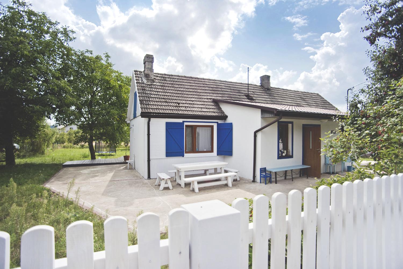 renowacja starego domu, niebieskie okiennice, biały drewniany płot, biały domek, drewniany dom